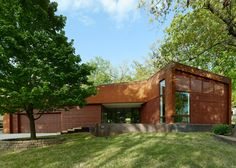 This ranch-style house in Arkansas has been dramatically revamped by covering the front facade in cedar and Corten steel, and adding an angular extension.