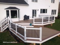 Vinyl deck with steps using @wolfbuilding  Tropical Hardwoods Collection PVC Decking with Amberwood flooring and Rosewood border, white PVC railing with black square aluminum balusters.