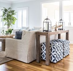 Living room with linen couch, navy and white poufs, driftwood tables, and blue accents.