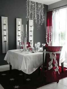 Holiday Festivities: Burgundy-red and metallic silver were combined to create a festive holiday dining room. Silver-beaded candelabras and sparkling snowflakes jazz up a plain white tablecloth. Burgundy fabric and silver ribbon adorn the chairs for a simple holiday makeover.