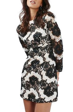 Transparent long sleeves frame this Topshop chic jewel-neck minidress crafted from wavy black-and-white guipure lace.