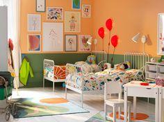 Kinderzimmer mit zwei ausziehbaren MINNEN Bettgestellen mit Federholzrahmen in Weiß, einem Tisch und Stühlen. Die Wände sind grün und orange gestrichen.