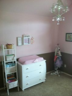 Brown and pink nursery with chandelier, chair rail, white furniture.#potterybarnkids