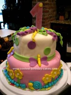 Homemade First Birthday Cake: This first birthday cake is fondant covered with snails, flowers, and butterflies made from fondant.   The top is a one I cut out with gum paste and the