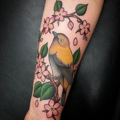 Yellow bird on cherry blossom branch by @cobraclubtattoo