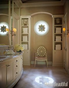 Master bath designed by J. Randall Powers. Love the antique starburst mirror hung in the round window, the limestone floors, marble countertops, and alabaster urns.
