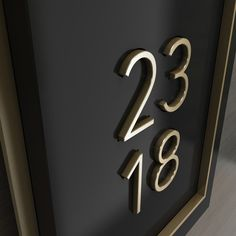 Detail view of a unit number in painted acrylic and brushed brass.