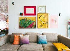 A sala de estar desse apê tem sofá cinza com almofadas coloridas e parede com composição de quadros.