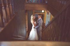 Bride and groom on stairs at Eighteen Ninety. Wedding and reception venue in Kansas City, Missouri. Photo by Paige Fish Photography.