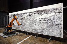 robotlab – Das zentrale Element in 'the big picture' ist ein kreativer Prozess, der die menschlichen Möglichkeiten übersteigt. In einem monatelangen, permanenten Arbeitsprozess fertigt der Roboterkünstler eine grossformatige Zeichnung an, die nur aus einer einzigen, ununterbrochenen Linie besteht. Mit seiner unnachahmlichen Technik erschafft er so ein einzigartiges Kunstwerk von unerreichbarer Detaillierung und Präzission.