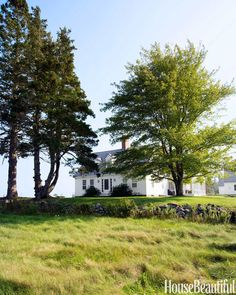 This Maine farmhouse was originally constructed in 1813. The original stone wall frames the lawn.