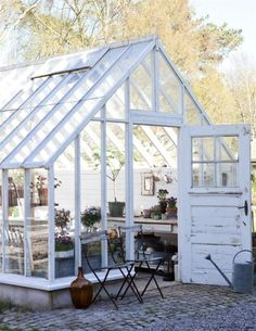 Beautiful white rustic greenhouse in Sweden. Inside is a seating area and small stove for a little extra spring warmth.