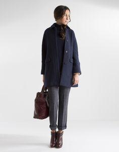 Abrigo corto azul de mujer, cuello camisero, cierre frontal con botones ocultos y dos bolsillos tapeta laterales en parte baja.