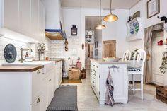 W tej rustykalnej kuchni z wyspą uwagę zwraca urokliwa podłoga. Stare deski odświeżono, malując je w pastelowe romby. Każdy skrawek ściany przeznaczono do zawieszenia ozdób czy praktycznych drobnych mebli, jak choćby nadstawka z przegródkami na talerze.
