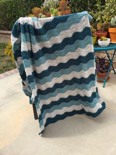 This blanket is a handmade, crocheted blanket. The ripple stitches create a wavelike pattern in light grey, soft blue and deep ocean turquoise.