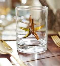 Coastal glasses from the Elegant Coastal Collection: http://www.completely-coastal.com/2016/05/5-coastal-nautical-theme-table-settings.html Gold starfish on drinking glasses.