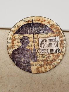 Artist trading coin created with an old bookpage and Tim Holtz stamps and paints.