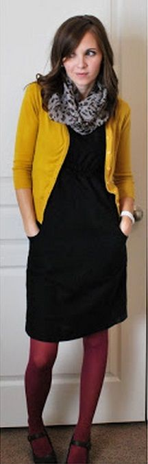 Little black dress shown, mustard cardigan, gray print scarf at neck, burgundy tights, black shoes.