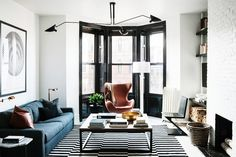 A blue couch, hanging art, square coffee table, orange armchair, large windows, black and white rug, black chair, marble side table, black ceiling lights