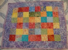 Doll Size Quilt or Table Topper in Batiks with Lavender Border  I used a variety of batiks, featuring blue, turquoise pale red, orange, yellow,