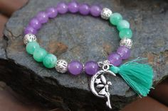 What you see is what you get - this is the only one of this bracelet I will make! Get it before its gone! - 8mm green and white kunzite beads. - 8mm purple alexandrite beads. - 8mm silver tone filigree hollow beads. - Silver tone fairy charm and accents. - Green tassel. - 6.5 Inches un-stretched (approximately). This bracelet best fits people with a small/medium frame. - Ships from Canada.  The bright and fun colors on this bracelet, complete with a cute fairy charm and tassel, will…