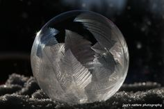 """Frozen bubble-Jocelyne Dupuis, image of a frozen soap bubble. """"Frozen bubbles are beautiful Mother Nature's Art, interesting to make but not easy. I make my own bubble mixture and blow the bubbles with a straw. The weather needs to be approximately -18 to -22 degrees Celsius (approximately 0 to -7 degrees Fahrenheit). Less cold will not produce as detailed art, and if it's too cold they will burst before freezing. Each bubble has as a different pattern of foliage frost like art."""""""