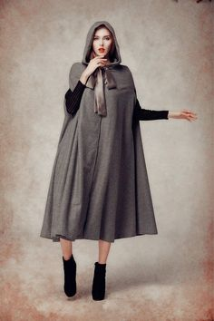 hooded cape long wool coat for women high end fabric fully lined a button on the fastening with neck belt oversized hooded design, flattering dress bottom strong sense of presence  This design belongs to our Moments Like This series. What will you take you back to those sweet moment? We discussed it warmly when we planned to make something special enough for the coming Christmas and chilly winter. serious 1950s? traitorous 60s? or colorful 80s? There was a time we immersed in the tranquility…