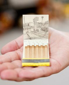 Artist Krista Charles, who has been collecting vintage matchbooks ever since inheriting a stash from her grandfather-in-law, draws intricate landscape illustrations on the inside cover of matchbooks. For each matchbook she tracks down the address of the business using Google Maps and makes a sketch of whatever is now shown at this location.