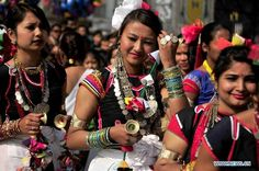 """Nepalese Tharu women dressed in traditional clothes join in celebration of the """"Maghi Festival"""" in Kathmandu, capital of Nepal, on Jan. 14, 2013. Maghi Sankranti is celebrated by Nepalese on the first day of 10th month in Hindu Lunar Calendar to mark the half of Winter and the start of New Year for Tharu community. (Xinhua/Sunil Pradhan)"""