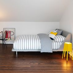 I don't think this is a DIY, but I think that it could be. The headboard looks like a couch. You could buy an old couch, only upholster the body of it, then build a bed frame the same height as the couch legs.