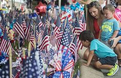 Rachael Hendrickson and her son, Chattanooga, Tenn. natives, kneel to view the memorial at the Armed Forces Recruitment Center.