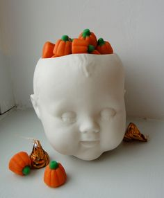 This one is ceramic, but for a cheap halloween candy dish, I could cut the top off of a thrift store doll head and spray white for a couple of dollars.   creepy indeed