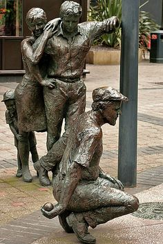 'The Boules Player' - bronze sculpture by artist Roger Burnett (2000);  a young family is observing the game of Boules;  located in Bond Court, Leeds, England;  photo by Georgina Collins