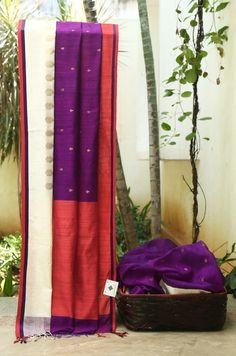 Purple matka silk by Bailou embellished with small gold butties. The saree has a white and red ganga-jamuna border than complements the body beautifully