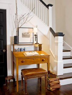 A petite writing desk, embellished with a few personal touches, has a charming presence in this small foyer./