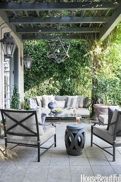 Neutral outdoor patio by Mary McDonald with modern lighting, grey sofa and armchairs, and a cutout Chinese garden stool.