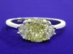 Diamond ring with 1.22-carat cushion modified brilliant cut diamond graded Fancy Yellow color, VS1 clarity, depth 69.8%, table 60%, Very Good polish, Good symmetry, No fluorescence, measuring 6.52 x 5.63 x 3.93 mm, ratio 1.15 prong set in an 18-karat yellow and 14-karat white gold three-stone basket-style mounting with a pair of crescent half moon cut diamonds having 0.34 total carat weight. The shank measures 1.7 mm wide at the baskets, 1.9 mm wide at the sides, and 1.7 wide at the bottom.