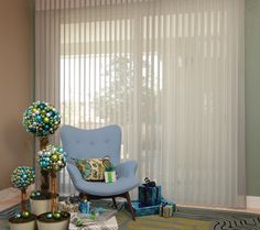 Give the holidays a special tint of color with glimmering ornament topiaries and Luminette® Privacy Sheers. ♦ Hunter Douglas window treatments #LivingRoom #HolidayDecor #Blue