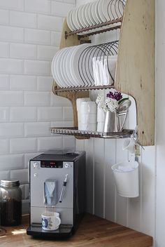I really love the stark white tiles and paneling, and the hanging coffee cups and plates. Great, vibey little corner. - Little Emma English Home.