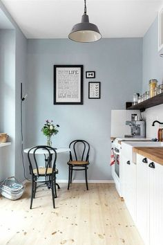 repeindre sa cuisine en bleu pastel, quelle couleur pour les murs d'une cuisine, luminaire gris foncé en style industriel, deux chaises de bistrot noires, en style rétro, avec des dossiers, sol revêtu de parquet lisse en PVC, en couleur beige, avec des petites taches marron