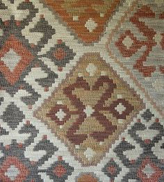 Kilim Upholstery Fabric Heavy weight upholstery fabric in the style of a turkish rug, in brown, terracotta and yellows, with a light beige background.