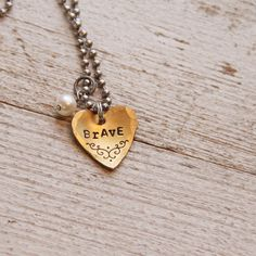 A sweet little golden heart is hand stamped with the word