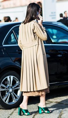 A delicate dress is layered under a pleated trench coat, and worn with satin Gucci mules