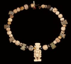 Necklace of thirty-five beads and composition pendants. Central pendant of Bes. Seven moulded pendants in green or blue faience of the head of Bes, with two pairs of suspension holes in the back; the heads are not completely identical. Twenty-six eye beads. Three oblate spherical beads of blue or dark glass appearing black. taly,Sardinia,Oristano (province),Tharros 8thC BC-3rdC BC. Culture/period: Phoenician.