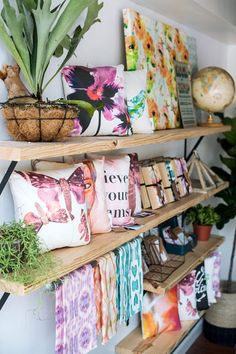 Gorgeous watercolor art and botanical illustration pillows and tea towels by designer Michelle Smith in the previous location of her shop Gather Goods Co in downtown Cary, North Carolina. Her newly relocated Gather Goods Co space in downtown Raleigh, North Carolina features her products alongside other emerging makers in a tiny shop and classroom area. The shelves here were made with untreated pine shelves and black brackets. Styling, shop and products by Michelle Smith, photo by Lissa…