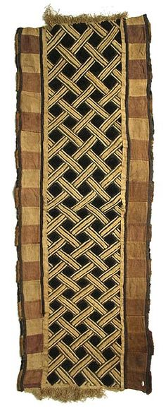 Kuba long cloth panel.  DR Congo | This special wrap, made from raffia, was worn outside, or on top of, the long dance dresses for added decoration and prestige. Made from raffia.  They incorporate embroidered shapes and patterns, openwork, tie-dye, tightly tufted areas and border elements. Most are covered with geometric symbols; many are restrained, subtle and rhythmic designs using one technique; others create amazing quilt-like assemblages of old pieces of many forms.