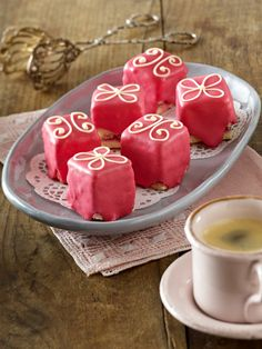 Petit Fours mit rosa Zuckerguss und Schokoverzierung  Zutaten (40 Stück)  4 Eier, 125 g Zucker, 1 Päckchen Vanillinzucker, 75 g Mehl, 50 g Speisestärke, 1 gehäufter TL Backpulver, 5 EL Kirschkonfitüre, 2 EL Aprikosenkonfitüre, 150 g Marzipan-Rohmasse, 1,5 EL + 400 g Puderzucker, 2 Eiweiß, rote Lebensmittelfarbe, 25 g weiße Kuvertüre, Backpapier, 1 Gefrierbeutel