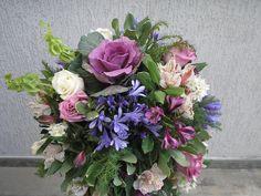 Centro de mesa bajo, en rosas lilas y  blancas, agapantus y astroemerias.