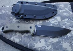 The Esse 5 is a extremely solid survival knife and is a top pick for many folks in the field. The Esse is about 11 inches long with a 1/4 inch thick 1095 carbon steel blade at 5 1/4 inches long. The Blade is powder coated for finish and durability and has a saber grind which keeps the blade thickness all the way out to the point. The ESEE heat-treatment process makes these 1095 carbon steel blades unique and some of the best 1095 that you can find.