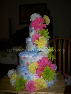 USE BOTTLE OF DREFT AS CENTER/CORE OF CAKE.  CAN FOLD DIAPERS INSTEAD OF ROLLING ALL OF THEM. USE BLANKET OR RIBBON TO SECURE THEN DECORATE. USE ITEMS INSTEAD OF FLOWERS THOUGH!